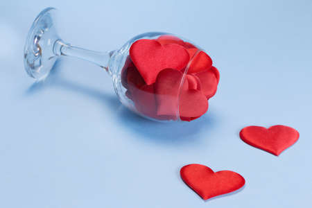 A glass full of satin red hearts on a blue background. Valentines day concept. Happy Valentines Day. Postcard. Copy space.