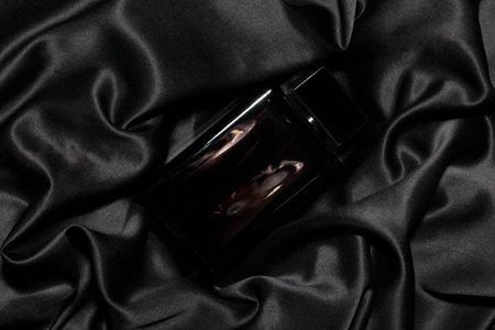 A perfume bottle of dark glass on satin black fabric. Low key. Imagens