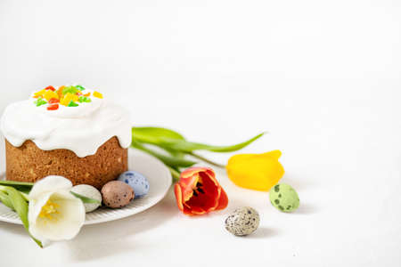 Easter composition with traditional Easter cake, painted quail eggs and tulips. Selective Focus