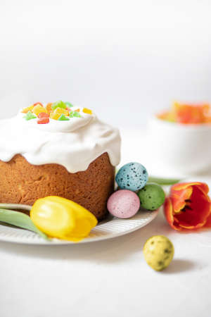 Easter composition with traditional Easter cake, painted quail eggs and tulips. Selective Focus Imagens