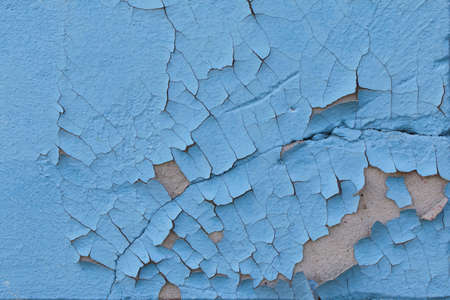 Cracked blue paint on an old cement wall. The old background is painted blue on the walls.