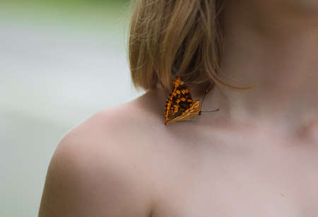 A butterfly sits on the naked shoulder of a young girl. 스톡 콘텐츠