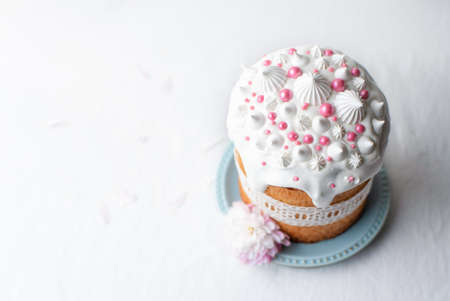 Traditional homemade Easter cake, decorated with glaze, pastry sprinkles and lace ribbon on a blue plate on a white table. Happy Easter. 스톡 콘텐츠