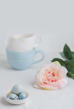 Painted quail eggs in a small white plate on a white table. Blue and white tea cups and a pink flower in the background. Happy Easter. Selective focus. Vertical photo.