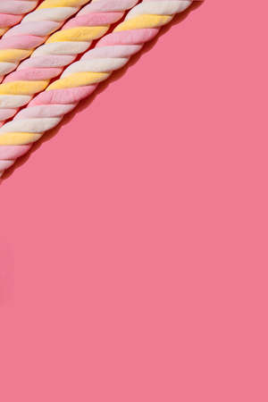 Border of spiral marshmallows on a pink background. Copy space.
