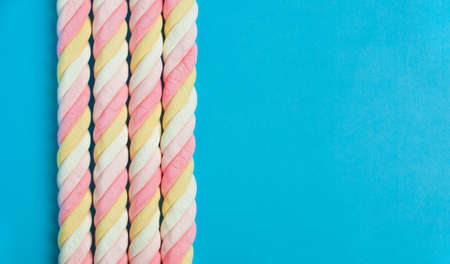Border of spiral marshmallows on a blue background. Copy space.