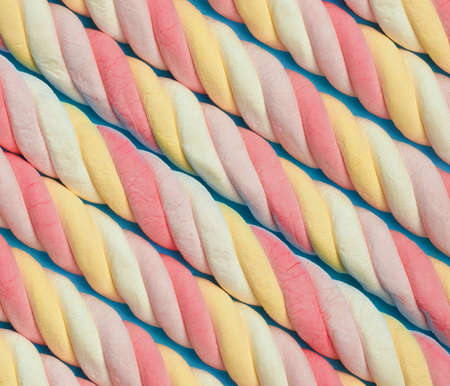 Marshmallow background. Sweet candy colorful diagonal texture. Rainbow colored marshmallow twists.