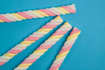 Spiral marshmallows on a blue background. Copy space. 스톡 콘텐츠