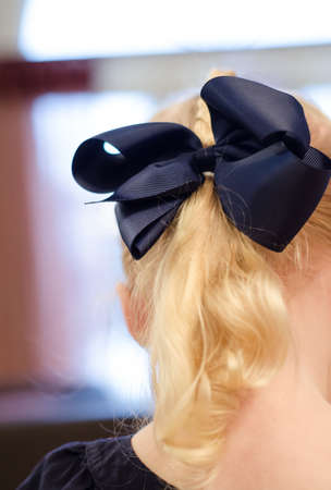 hair bow: A blue bow in a childs long blonde hair.