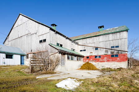 barnyard: A barn sits in the corner of a barnyard on a clear blue sky day. Editorial
