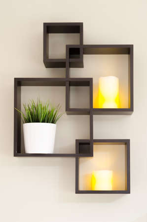 creativity: A shelf on the wall holding two candles and some potted green grass. Stock Photo