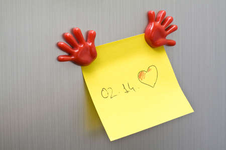Post it reminder for Valentine Days on a memo board with magnet hands.