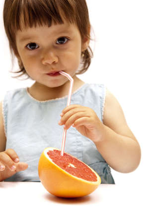 little girl drinking a grapefruit juice Imagens - 5015981
