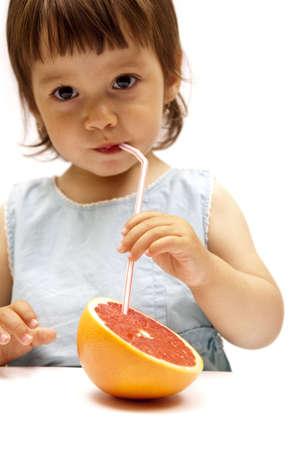 little girl drinking a grapefruit juice