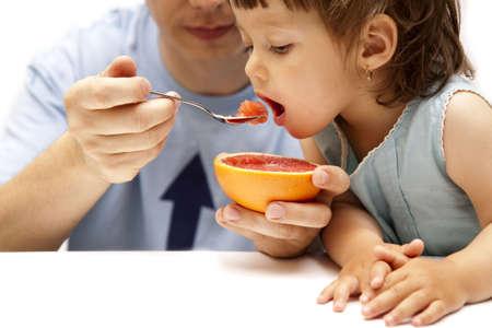 little girl eating a grapefruit photo