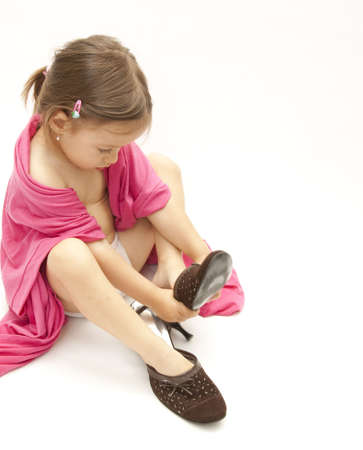 little girl dressing with her mother shoes and cloths