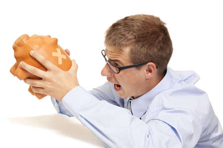 Engry business man shaking the piggy bank