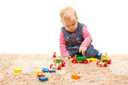 cute little girl playing with wood toys photo