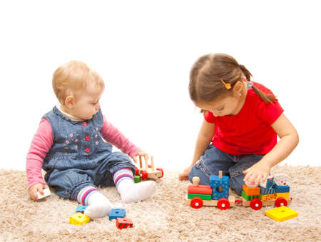 adorable sisters playing with wood train photo