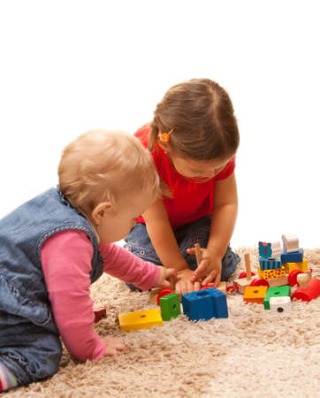 sisters playing on the floor with wood toys photo