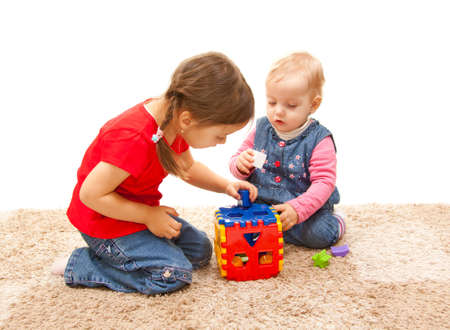 sisters playing on the floor with cube toy photo