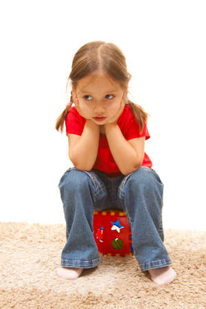 isolated cute girl sitting on a plastic toy