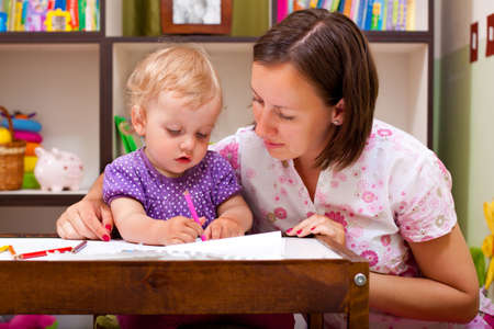 mother and her daughter, drawing with pencils Stock Photo