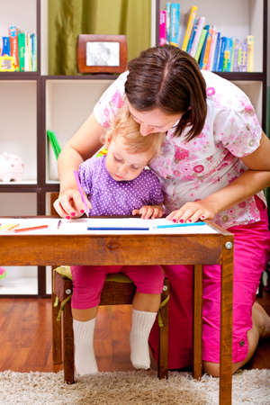 Mother helping her daugter to draw Imagens - 9641856
