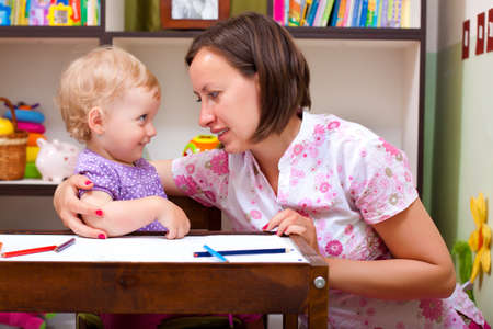mother and her daughter playing in the child room Imagens
