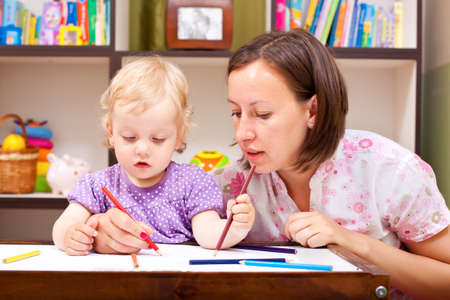 Mother helping her daughter to draw Stock Photo