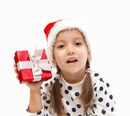 little girl holding a red box in christmas time photo