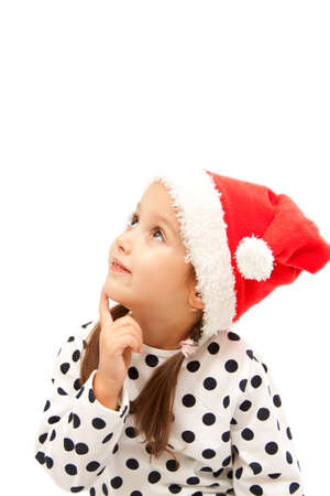 smile girl with a red santa hat dreaming photo