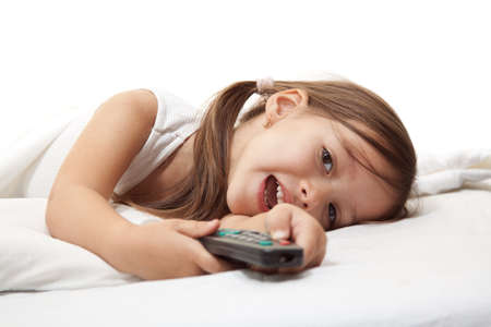 little cute girl in the bed, with a remot control in hand