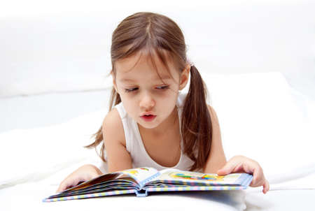 little girl reading a book on the bed Stock Photo