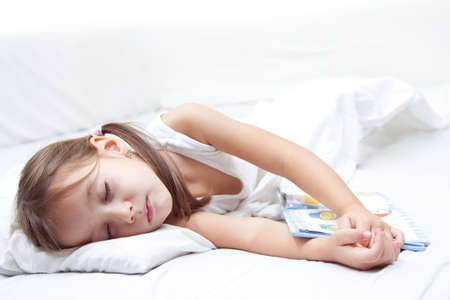 tired little girl sleepig, with hand on book, in the bed Stock Photo