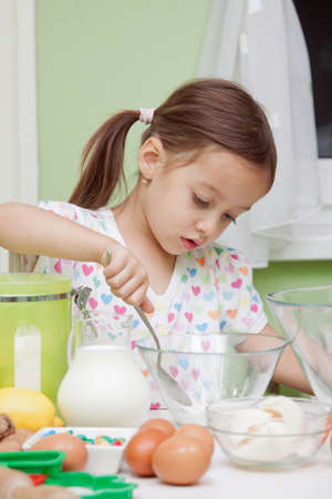 Beautiful young Girl Working in the Kitchen baking  photo