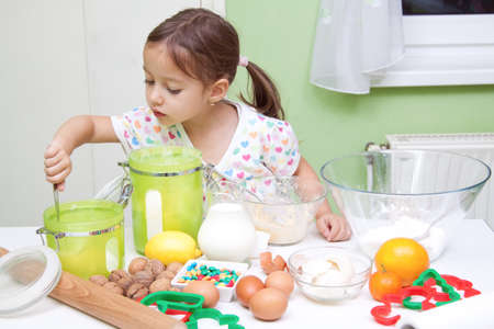 little girl bakeing in the kitchen Stock Photo