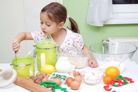 little girl bakeing in the kitchen Imagens