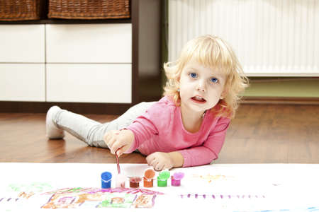 little finger: Baby girl with blue eyes paint in the floor
