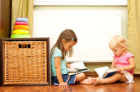 daycare: sister on floor reading a book - edication concept