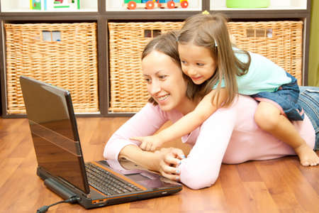 mother and het daughter have fun in front of laptop
