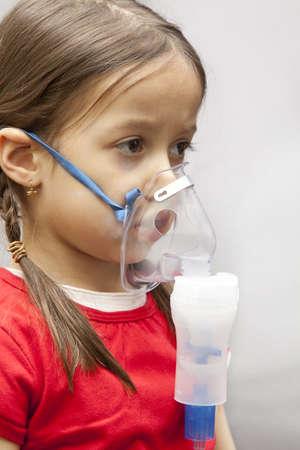 respiracion: la inhalaci�n de m�scara en una cara de la muchacha Foto de archivo