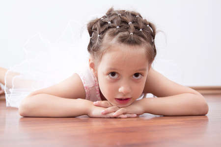 Beautiful little balerina laying on the floor photo