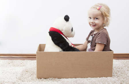 blond little girl with her teddy bear ready to move Stock Photo