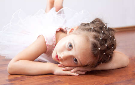 little ballerina laying on the floor photo