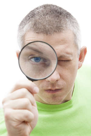 Funny young man in a green t-shirt looking through magnifying glass