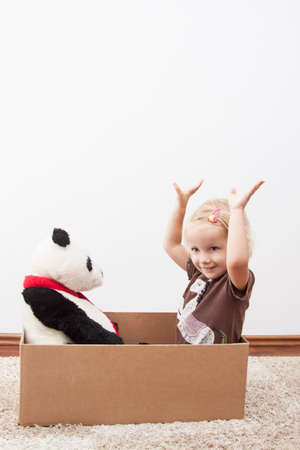 cardbox: little girl is happy to move, with panda bear on cardbox Stock Photo