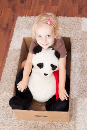 cardbox: smile girl in a cardbox with her panda bear - ready to move