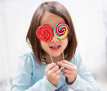 Little girl playing with two colored lollipops Imagens