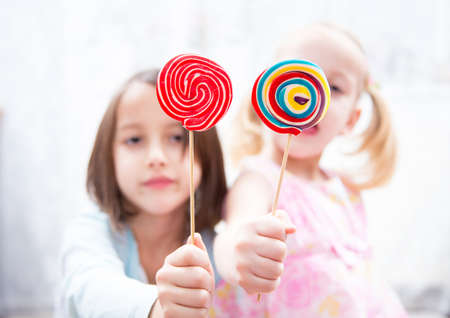 provocative food: Little girls have fun with colored lollipops